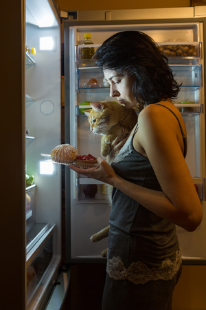 fridge: Woman and cat at night looking for food in the fridge