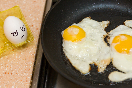 expresiones faciales: The painted eggs look at cooking eggs in a frying pan