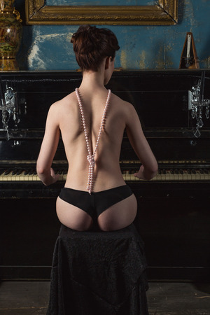nude black woman: Naked woman plays the piano, the view from the back