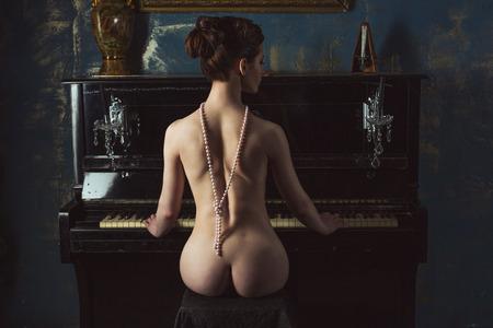 Обнаженная женщина играет на пианино, вид сзади