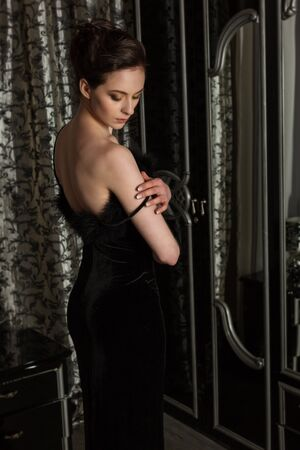 woman undressing: Elegant woman undressing, black evening dress in front of a mirror in the bedroom Stock Photo