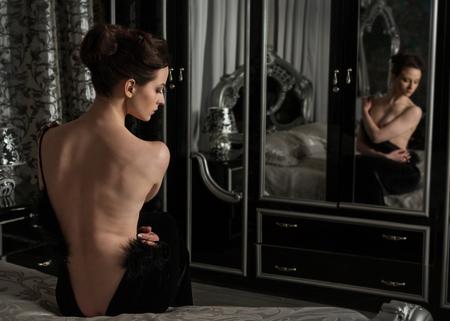 vestido de noche: desvestirse mujer elegante, vestido de noche negro delante de un espejo en el dormitorio