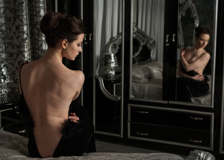 Elegant woman undressing, black evening dress in front of a mirror in the bedroom Stock Photo