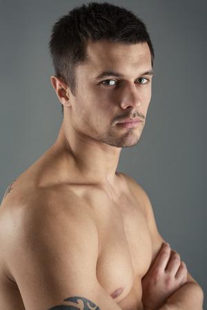 homme nu: Portrait d'un beau jeune homme sur un fond, vue gris c�t�.