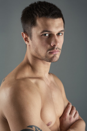 hombre desnudo: Portrait of a handsome, young man on a gray background, side view.