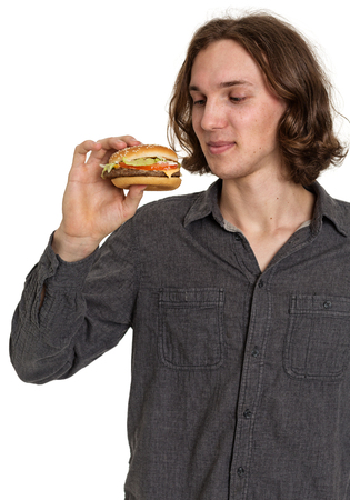 adult sandwich: Young man eating a hamburger from fast food, isolated on white