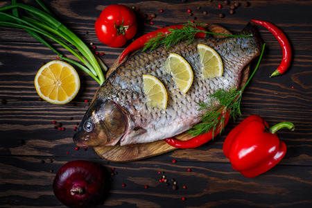Carp fish with fresh vegetables on a dark, wooden table Stock Photo