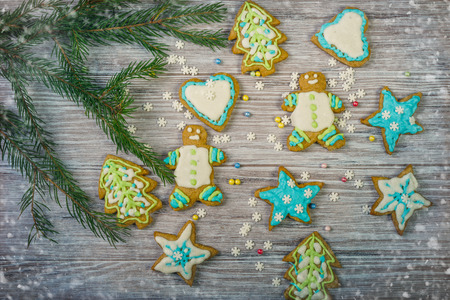 Glazed Christmas gingerbread and Christmas tree branches on a wooden background Foto de archivo
