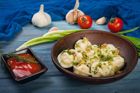 Dumplings in clay plate on blue, wooden background Stock Photo