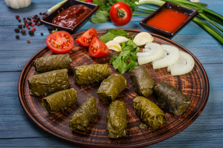 Dolma in grape leaves and vegetables on wooden background