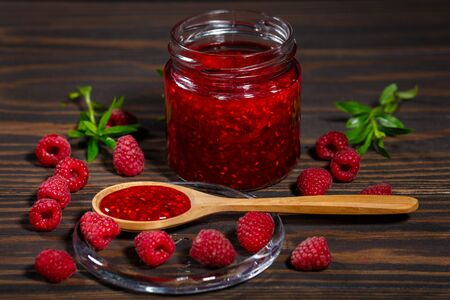 Jar of jam and ripe raspberry berries on a dark, wooden background