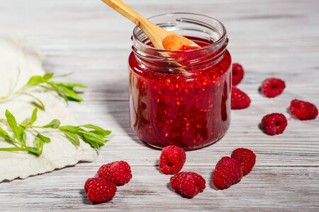 Homemade jam and fresh raspberry on wooden background