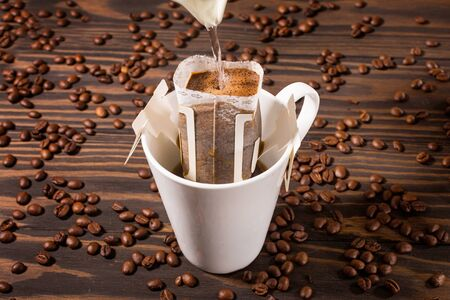 Brewing coffee in a Cup through a filter, on a dark wooden background