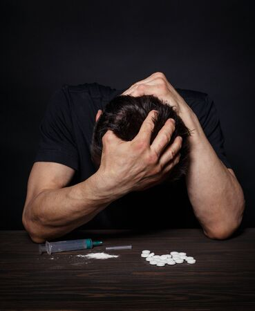 Man in despair from drug addiction is sitting at a table
