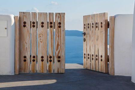 Wooden gates close access to the sea. Greece, Santorini island