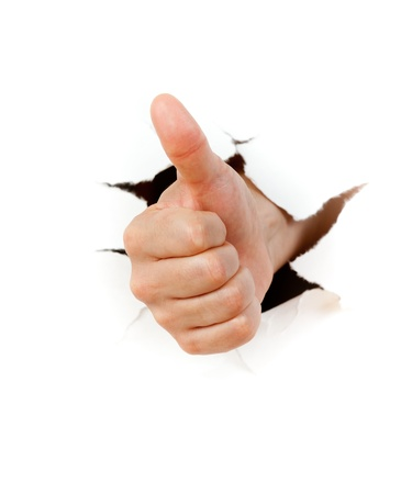 Hand with thumb up through a hole in paper Stock Photo - 10806509