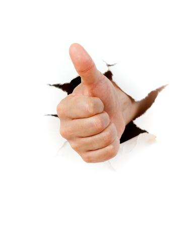 pulgar levantado: Mano con el pulgar hacia arriba a trav�s de un agujero en el papel Foto de archivo
