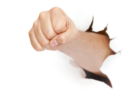 powerful creativity: fist punching through paper isolated on white background