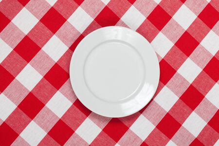 white round plate on red checked tablecloth photo