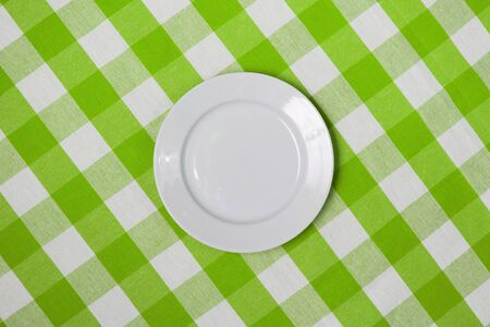 checker plate: white round plate on green checked tablecloth
