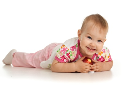 lying baby girl with red apple photo
