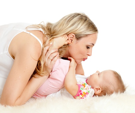 Loving mother kisses her child;  child is lying on sheepskin photo