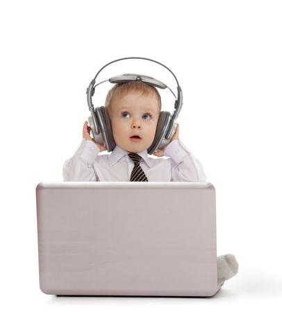 escucha activa: Ni�o divertido jugar con el ordenador port�til y escuchar m�sica en los auriculares