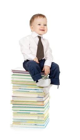 bebe sentado: ni�o vestido con traje y sentado sobre el mont�n de libros Foto de archivo