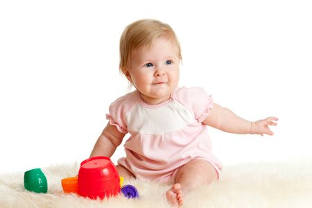 Cute little child is playing with toys while sitting on floor, isolated over white Stock Photo - 11327433