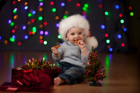 funny baby in Santa Claus hat on bright festive background Stock Photo - 11327456