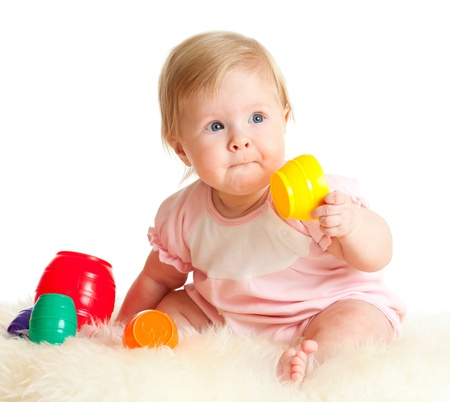 babies with toys: Cute little child is playing with toys while sitting on floor, isolated over white