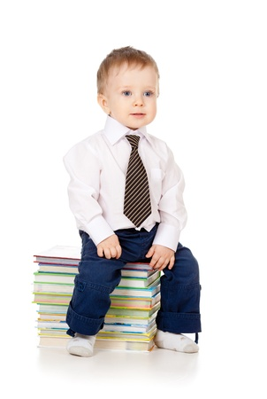 toddler dressed in suit and sitting on the heap of books photo