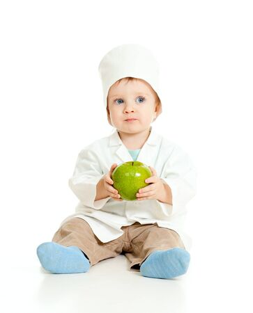 Adorable boy uniformed as doctor with healthy food over white photo