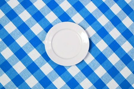 white round plate on blue checked tablecloth photo