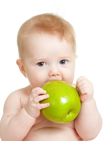baby eating: Baby boy holding and eating green apple, isolated on white