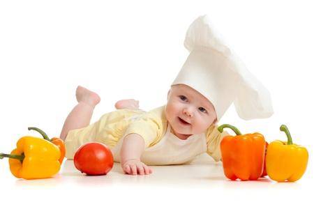 aliments droles: Portrait d'un b�b� portant un chapeau de chef cuisinier avec des l�gumes des aliments sains, isol� sur blanc