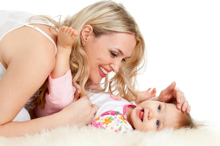 girl lying studio: Loving mother playing with her baby;  child is lying on sheepskin