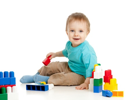 babies playing: little cheerful child with construction set over white background