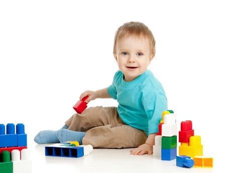 piccolo bambino allegro con la costruzione insieme su sfondo bianco Archivio Fotografico