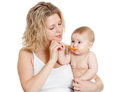 mother feeding  her baby by spoon photo