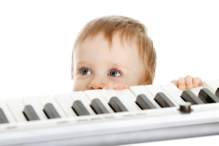 adorable child stanging behind electronic piano photo