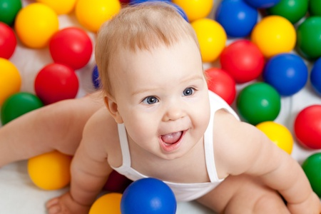 six month old: Portrait of a adorable infant sitting among colorful balls