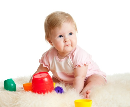 play blocks: Cute little child is playing with toys while sitting on floor, isolated over white