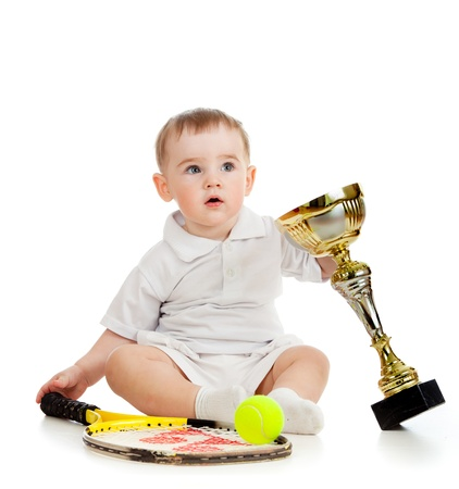 adorable child playing with tennis racket and cup over white background photo