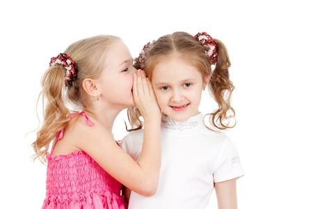 Little girlfriends sharing a secret isolated on a white background photo