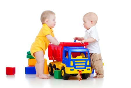two little children playing with color toys and truck Stock Photo - 12264774