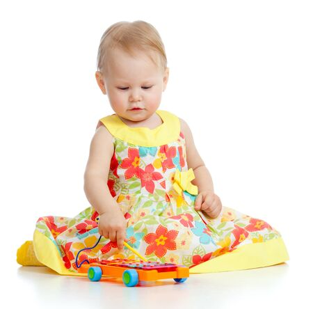 baby girl playing  with musical toys. Isolated on white background photo