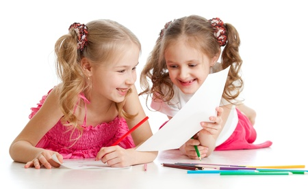 two girls drawing with color pencils together. Focus on the girl on foreground photo
