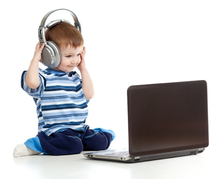 actief luisteren: Grappig kind speelt met laptop en het luisteren naar muziek in de koptelefoon