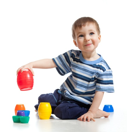 Cute little child is playing with toys while sitting on floor, isolated over white photo